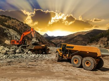 Excavator loading dumper trucks at sunset at mining site.