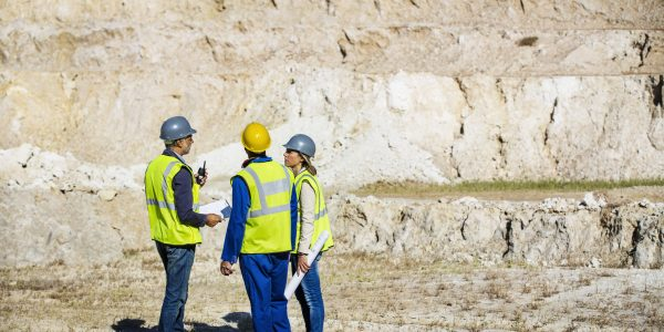 Full length of construction team in protective workwear discussing at quarry